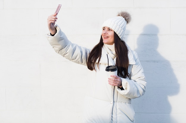 Beautiful girl taking selfie in outwear