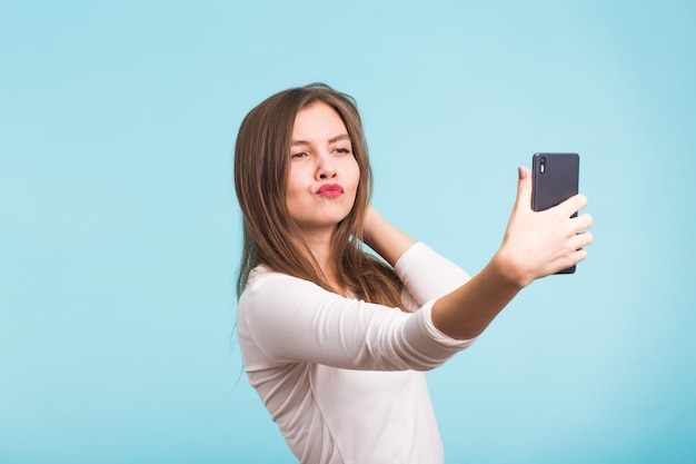 파란색 배경 위에 selfie를 복용하는 아름 다운 여자