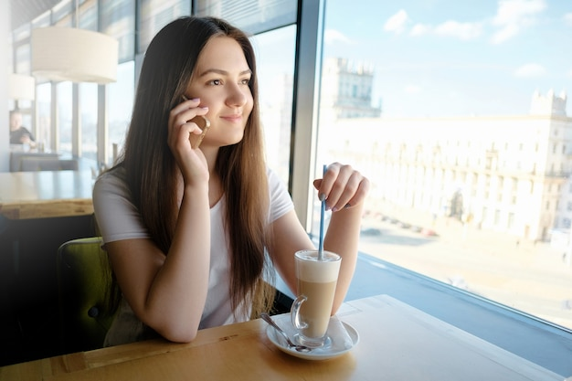 라떼와 전화로 카페에서 이야기하는 아름 다운 소녀