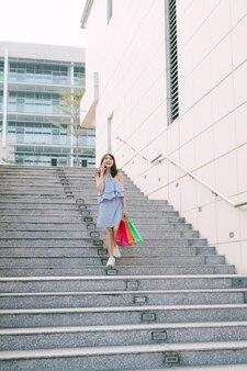 電話で話し、階段を下りながら買い物袋を持った美しい女の子。