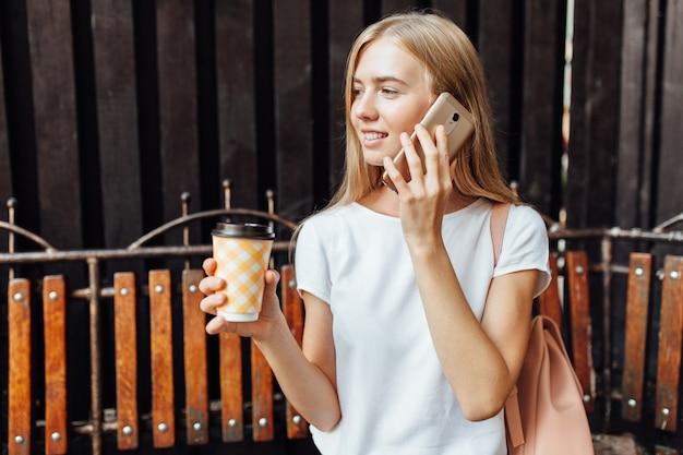 木製の落葉性壁の近くのベンチに座って、電話で話していると白いtシャツでコーヒーを飲みながら美しい少女