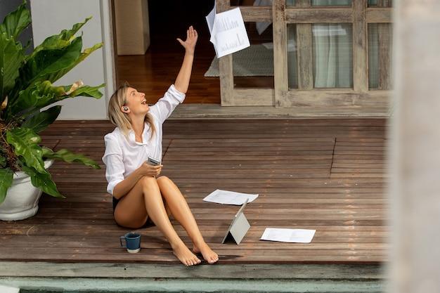 電話で話し、タブレットで作業している美しい少女。