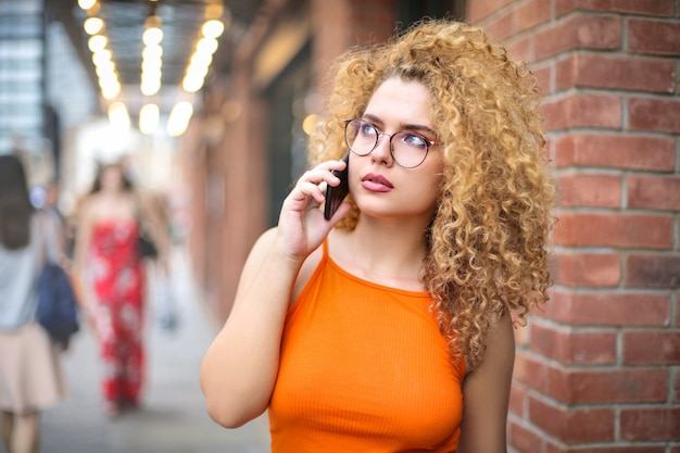 Beautiful girl talking at the phone while walking in the street