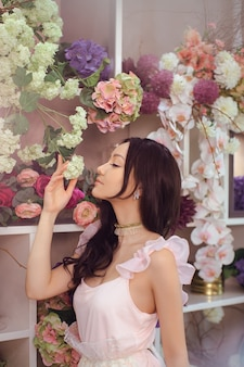 Beautiful girl in tender pink dress standing against floral in flower shop. joyful