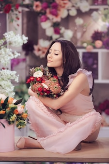 Beautiful girl in tender pink dress with bouquet flowers peonies in hands sitting on table