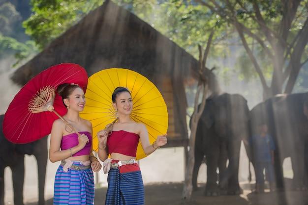 Красивая девушка тайской ланны женщины в платье со слонами