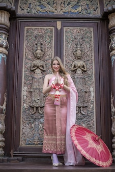 Beautiful girl in the thai national bright dress with oriental makeup travel in thailand