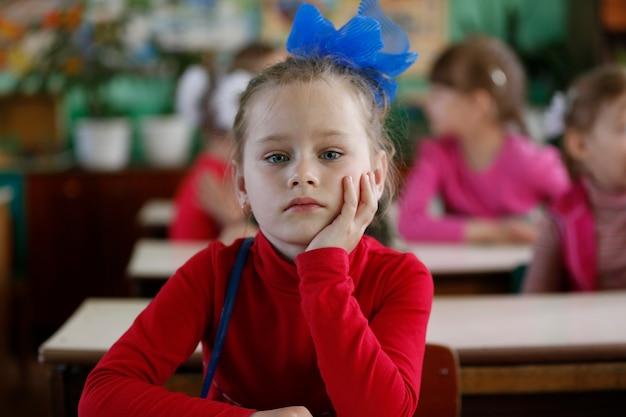 Красивая девочка, ребенок сидит за столом в детском саду. девочка дошкольного возраста