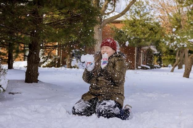 겨울 날에 목가적 인 집 마당에 눈이 내리는 행복한 소녀가 눈이 내리는 동안 아름다운 소녀가 눈덩이를 던졌습니다.