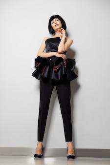 Beautiful girl in tight pants and peplum silk corset posing near white wall, she has dummy-style makeup and bob haircut