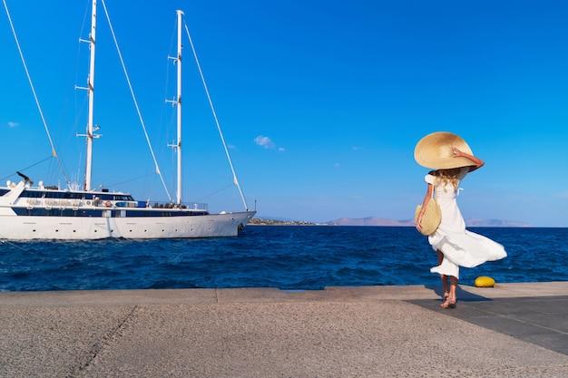 スペツェスマリーナ港ギリシャで歩く美しい少女観光客