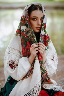 Beautiful girl in a traditional ethnic dress with an embroidered cape on her head