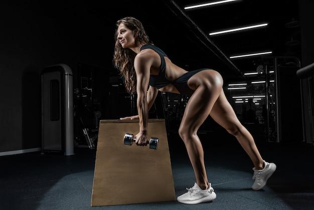 Красивая девушка тренируется в тренажерном зале с гантелями на скамейке. виды спорта,
