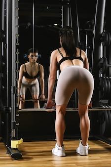 Красивая девушка тренирует ноги, тренировки в тренажерном зале, поднятие тяжестей, тренировка на ногах, приседания, удержание штанги, пауэрлифтинг, фитнес
