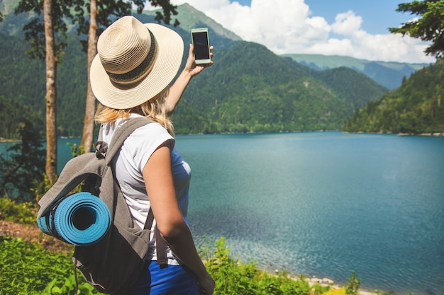Beautiful girl traveler in a hat stands on a lake and takes pictures on a background of mountains