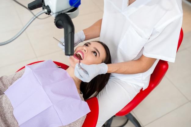 Beautiful girl treats teeth in dentistry.