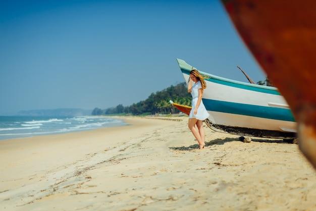 Beautiful girl on tropical beach near fisherman's boat.