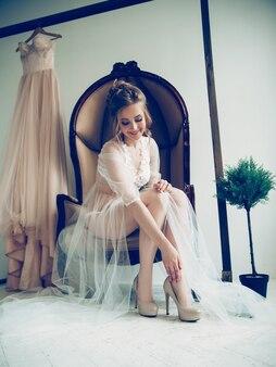 우아한 결혼식 신발에 노력하는 아름 다운 소녀.