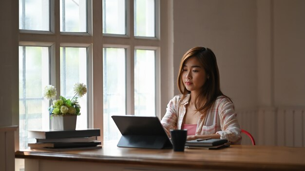 Beautiful girl typing on computer tablet with keyboard case while sitting at the wooden working table over modern and comfortable living room