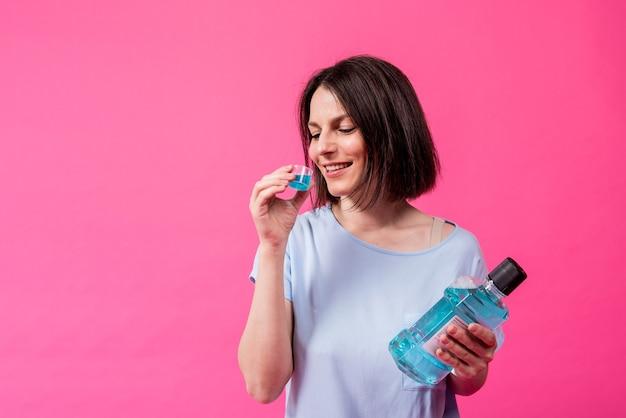 아름다운 소녀는 분홍색 배경에 구강 세척제를 사용합니다