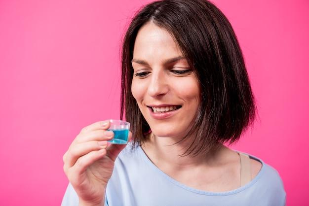 美しい少女はピンクの背景にうがい薬を使用しています