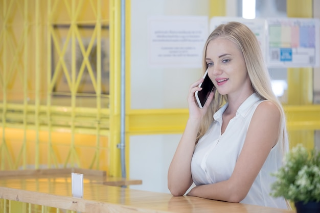 Красивая девушка с помощью своего мобильного телефона в кафе счастлива и улыбается.