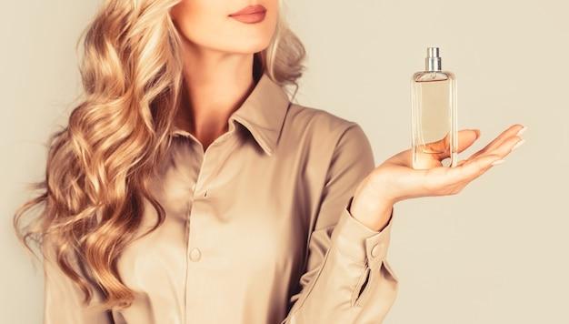 향수를 사용 하여 아름 다운 소녀입니다. 향수의 병을 가진 여자입니다. 여자 향수 향수를 선물합니다. 향수 병 여자 스프레이 아로마.