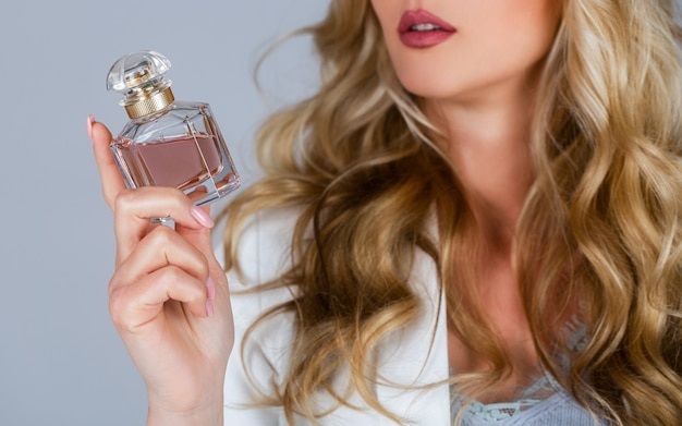 Beautiful girl using perfume. woman with bottle of perfume. woman presents perfumes fragrance. perfume bottle woman spray aroma. woman holding a perfumes bottle.