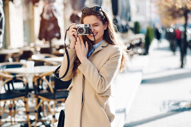 Beautiful girl in vintage photographs on the camera and walks in summer city