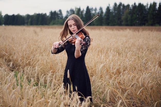 美しい少女のバイオリニストは、熟した麦畑でバイオリンを弾くことを楽しんでいます