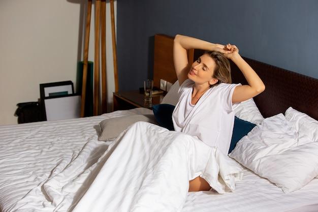 美しい少女がベッドで目を覚ます。