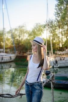 The beautiful girl on walk on the yacht club mooring