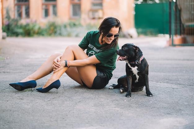 Красивая девушка гуляя ее собака стаффордширский бультерьер outdoors на солнечный день в лете сидит дорога.