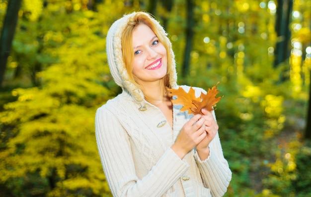 秋の公園を歩いている美しい少女。黄色の葉を持つ笑顔の女性。秋の天気を楽しんでいる女性。晴れた日。