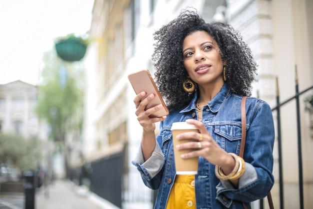 Красивая девушка гуляет на улице, проверяет свой телефон и пьет кофе