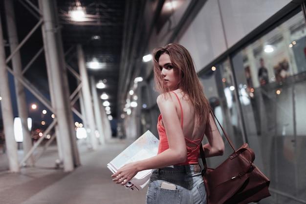 건물 근처를 걷고 돌아서 아름다운 소녀