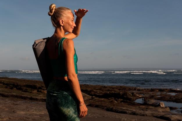 Красивая девушка гуляет по пляжу с ковриком для йоги
