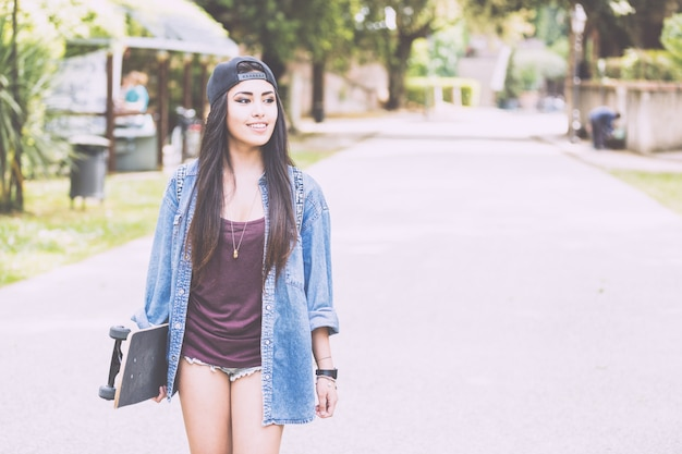 Beautiful girl walking at park holding a skateboard.