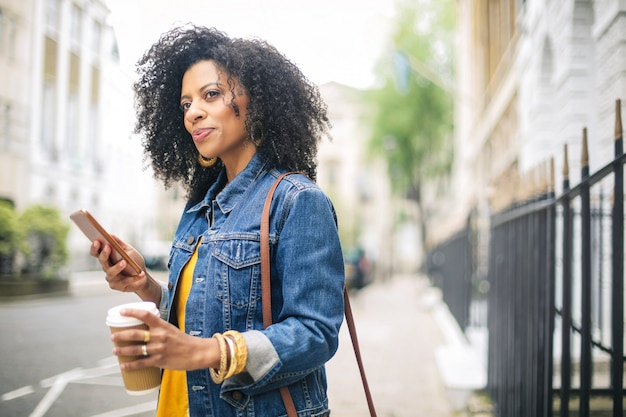 Beautiful girl walking in the street, checking her phone and drinking a coffee