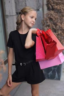 街で色付きのバッグを持って歩く美しい少女