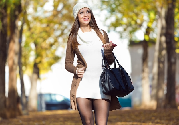 Beautiful girl walking with mobile phone in autumn.