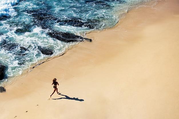 Bella ragazza cammina lungo la spiaggia selvaggia. incredibile vista dall'alto.