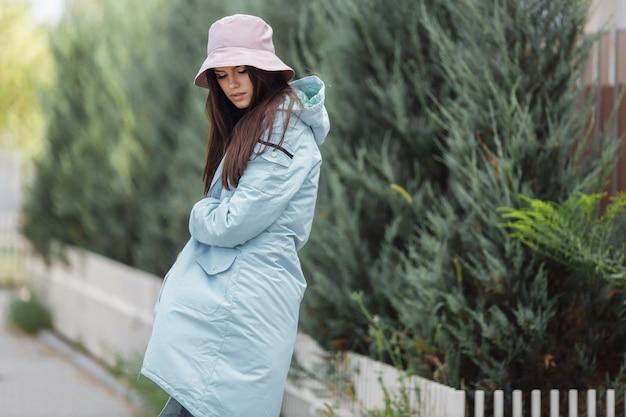 美しい少女が秋のコートを着て路地を歩く