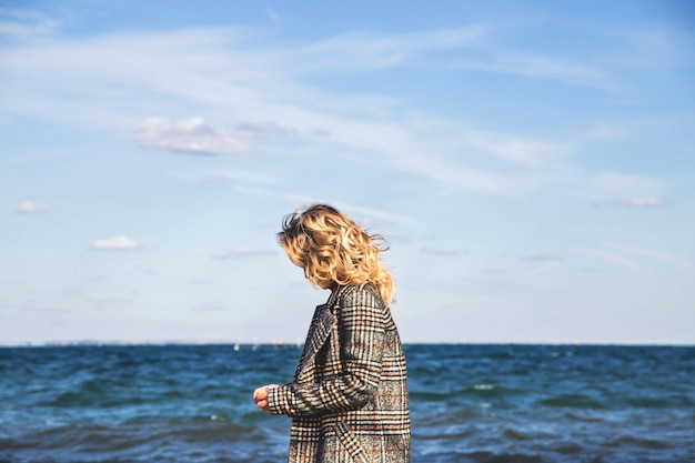 美しい少女は秋に歩き、海辺でマインドフルネスを実践します。