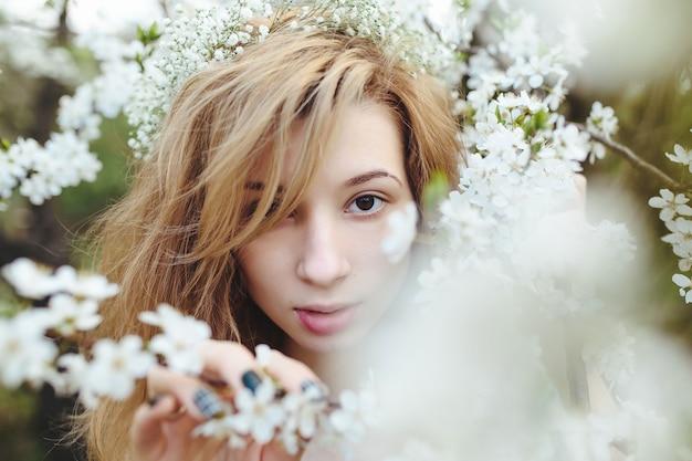 花輪に身を包んだ緑豊かな庭園を歩く美少女