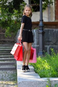 美しい少女は色付きのバッグを持って公園を歩く