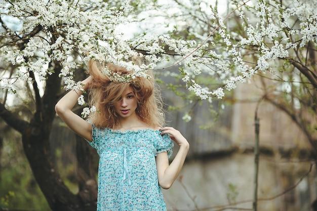La bella ragazza cammina nel giardino lussureggiante vestita con una ghirlanda