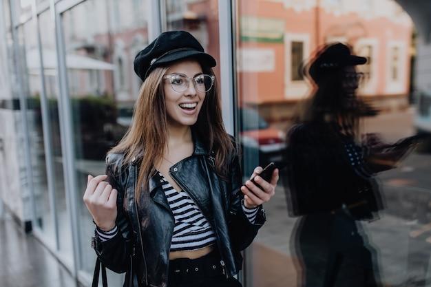 雨の後、美しい少女が黒い革のジャケットを着て通りを歩く