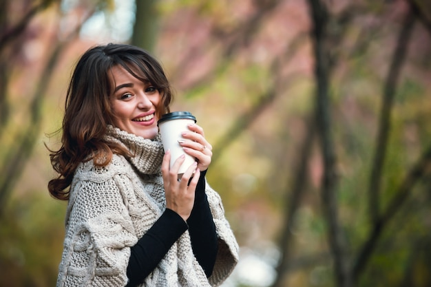 Beautiful girl in a warm sweater with a cup of coffee in the autumn park. warm sunny weather. outdoors.