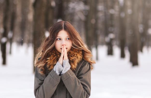 Красивая девушка согревает руки дыханием зимой в парке
